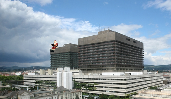 Huge Santa sitting and reading a book on the top of the Vienna General Hospital (Allgemeines Krankenhaus der Stadt Wien)